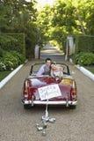 Couples de nouveaux mariés dans la rétro voiture de mariage Images stock