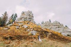 Couples de nouveaux mariés embrassant sur le paysage extérieur majestueux avec les roches massives comme backround Images stock