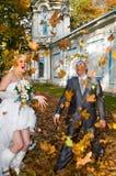 Couples de nouveaux mariés en stationnement d'automne Photo stock
