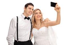 Couples de nouveaux mariés prenant un selfie avec le téléphone Photo stock