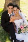 Couples de nouveaux mariés se reposant contre le tronc d'arbre en parc Photographie stock