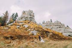 Couples de nouveaux mariés sur le paysage extérieur majestueux avec les roches massives comme backround Image stock