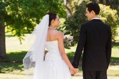Couples de nouveaux mariés tenant des mains et marchant en parc Image stock