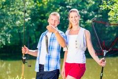 Couples de pêche, homme et femme, sur le lac étant fier du crochet Photo libre de droits