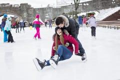 Couples de patinage de glace ayant l'amusement d'hiver sur des patins de glace Photographie stock