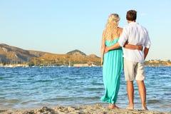 Couples de plage tenant des mains marchant au coucher du soleil Image stock