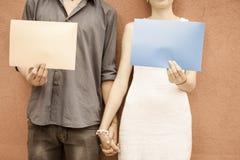 Couples de plan rapproché tenant des mains et tenant des cadres au fond de mur Images stock