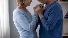 Couples de retraité tenant des mains, regardant l'un l'autre avec l'amour et la reconnaissance photo stock