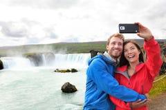 Couples de Selfie prenant la cascade de photo de smartphone Photographie stock libre de droits