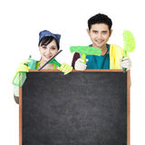Couples de service de nettoyage tenant le tableau noir Photo stock
