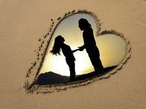 Couples de silhouette au coeur de sable Photos stock