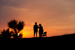 Couples de silhouette au coucher du soleil Photos stock