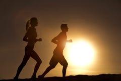 Couples de silhouette courus ensemble sur un coucher du soleil Photo libre de droits
