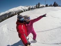 Couples de skieur sur le flanc de montagne neigeux Photographie stock libre de droits