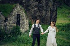 Couples de sourire élégants heureux marchant et embrassant en Islande, dessus Photo stock