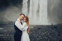 Couples de sourire élégants heureux marchant et embrassant en Islande, dessus Photographie stock