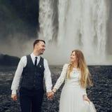 Couples de sourire élégants heureux marchant et embrassant en Islande, dessus Photos libres de droits