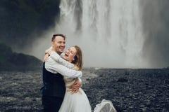 Couples de sourire élégants heureux marchant et embrassant en Islande, dessus Photos stock