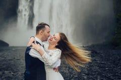 Couples de sourire élégants heureux marchant et embrassant en Islande, dessus Image stock