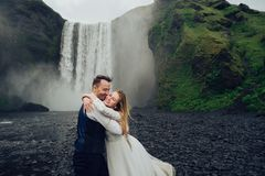 Couples de sourire élégants heureux marchant et embrassant en Islande, dessus Photographie stock libre de droits