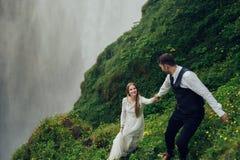 Couples de sourire élégants heureux marchant et embrassant en Islande, dessus Image libre de droits
