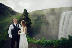 Couples de sourire élégants heureux marchant et embrassant en Islande, dessus Photo libre de droits