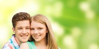 Couples de sourire étreignant au-dessus du fond vert Image libre de droits