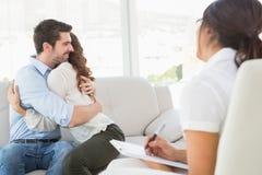 Couples de sourire étreignant devant leur thérapeute Image stock