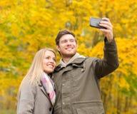 Couples de sourire étreignant en parc d'automne Photos libres de droits