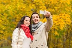 Couples de sourire étreignant en parc d'automne Images libres de droits