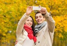 Couples de sourire étreignant en parc d'automne Photos stock