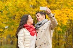 Couples de sourire étreignant en parc d'automne Image libre de droits