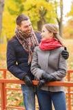 Couples de sourire étreignant sur le pont en parc d'automne Image libre de droits