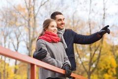Couples de sourire étreignant sur le pont en parc d'automne Photos libres de droits