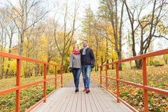 Couples de sourire étreignant sur le pont en parc d'automne Photo stock