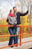 Couples de sourire étreignant sur le pont en parc d'automne Photographie stock