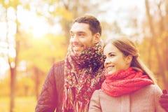 Couples de sourire étreignant sur le pont en parc d'automne Photographie stock libre de droits