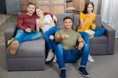 Couples de sourire étreignant tout en regardant la TV avec des amis Image libre de droits