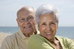Couples de sourire aînés à la plage Image stock