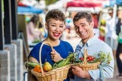 Couples de sourire au marché d'agriculteurs Images libres de droits