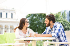 Couples de sourire ayant le mojito au café de trottoir Photo stock