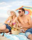 Couples de sourire ayant le pique-nique sur la plage Image stock