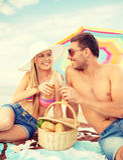 Couples de sourire ayant le pique-nique sur la plage Photo stock