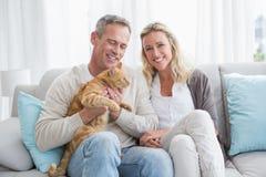 Couples de sourire choyant leur chat de gringer sur le divan photographie stock