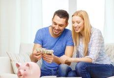 Couples de sourire comptant l'argent à la maison Photographie stock
