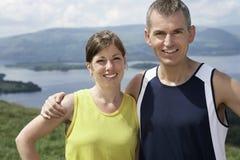 Couples de sourire contre le lac Photo libre de droits
