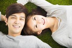 Couples de sourire détendant sur l'herbe verte Photo libre de droits
