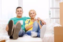 Couples de sourire détendant sur le sofa dans la nouvelle maison Images libres de droits