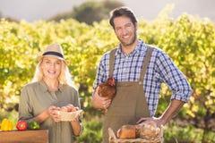Couples de sourire d'agriculteur tenant le poulet et les oeufs Photographie stock libre de droits