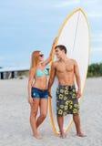 Couples de sourire dans des lunettes de soleil avec des ressacs sur la plage Images stock